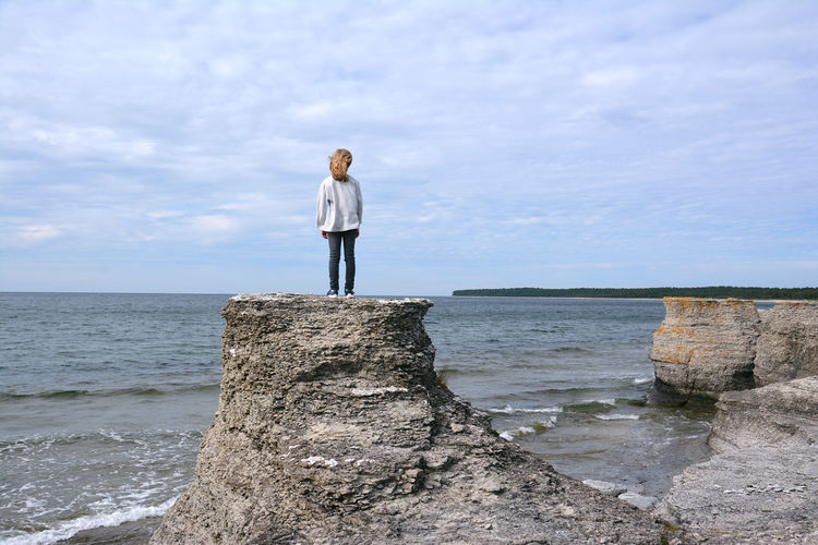 Rear View Of Woman Standing On Stack Rock By Sea Against Sky