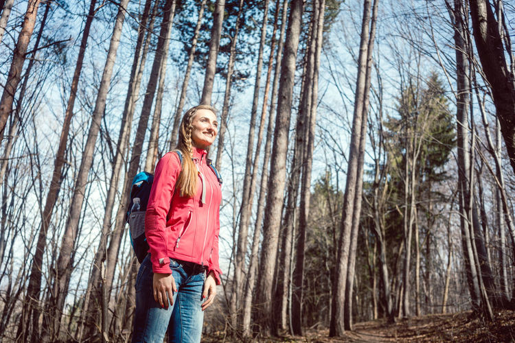 Low Angle View Of Smiling Woman Standing In Forest