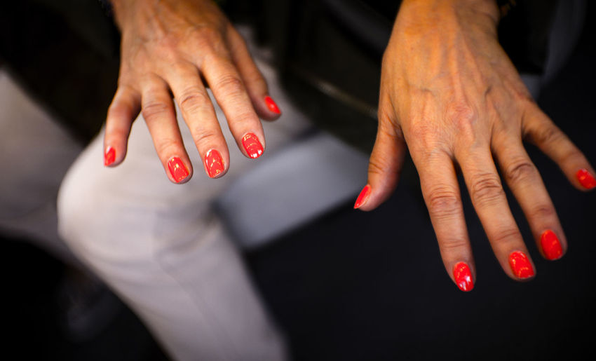 High angle view of woman showing painted fingernails