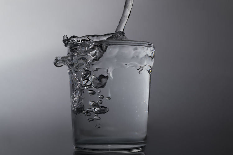 Glass with water Basic Bubbles Drink Drinking Glass Drinking Water Drop Food And Beverages Food And Drink Freshness Full Glass Glass Of Water Gray Background Motion Motion Blur No People Refreshment Single Object Spilling Splashing Studio Shot Water