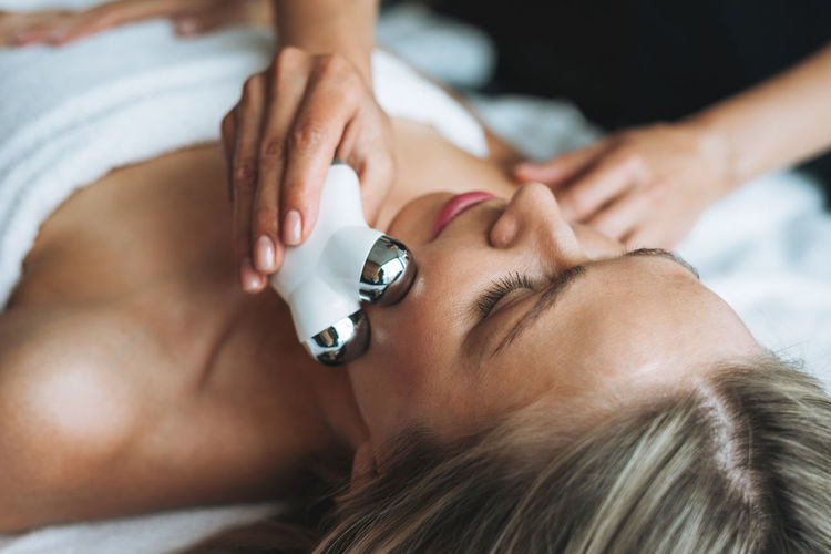 Young blonde woman enjoys facial massage with microcurrent facial massager in spa salon