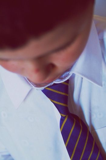 Close-up of boy wearing shirt and tie