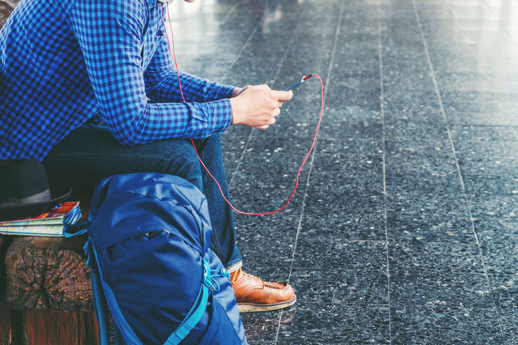Low section of man with luggage listening music while sitting at railroad station platform