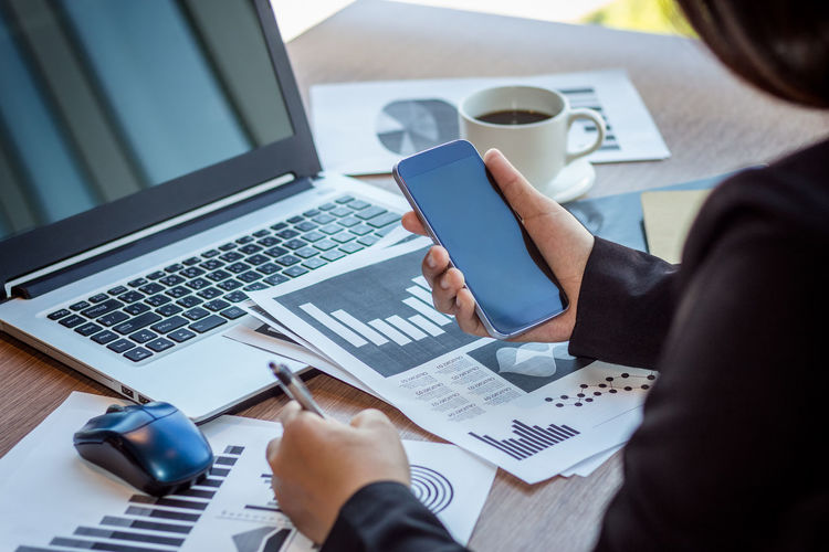 Cropped hands of businesswoman using phone at desk in office