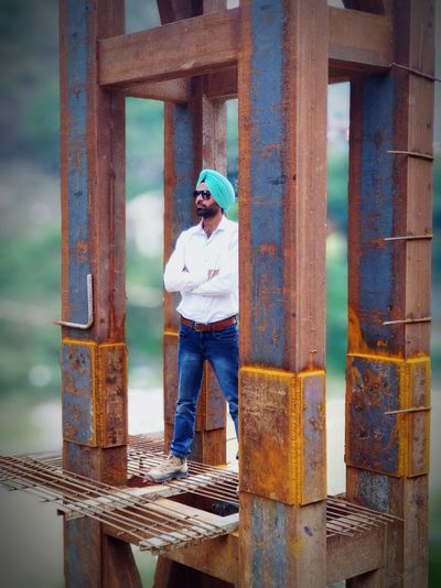 Man standing by metal structure