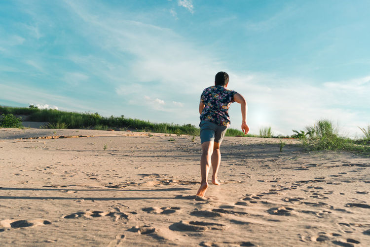 Rear view of man running on sand at beach