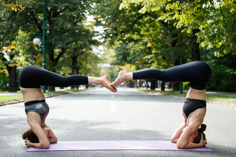 Full length of two women doing yoga on road