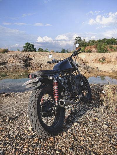 Motorcycle on dirt against sky