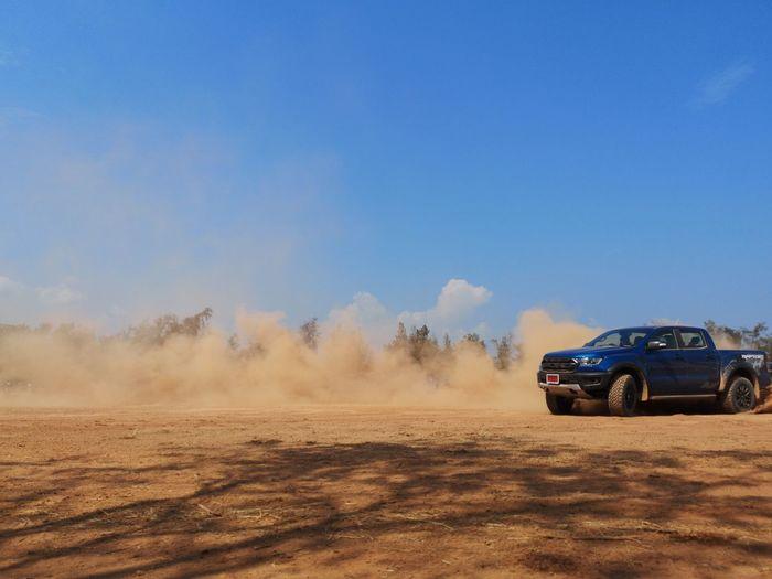 Car on field against clear blue sky