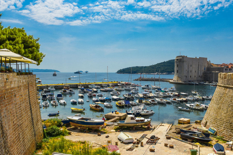 Old Harbor with City Wall and blue sky, Dubrovnik, Croatia Adriatic Adriatic Sea Architecture Boat Building Exterior Built Structure Croatia Day Dubrovnik Dubrovnik, Croatia Harbor High Angle View Holiday Mediterranean  Mediterranean Sea Nature Nautical Vessel No People Outdoors Sky Summer Tranquility Travel Destinations Tree Water