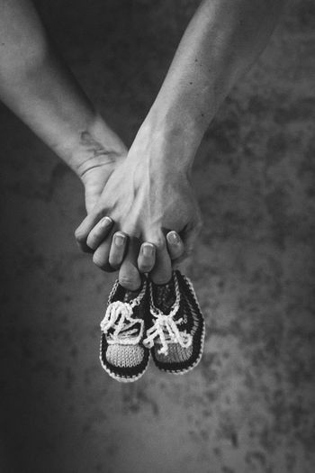 Two humans holding baby shoes Baby Shoes Holding Hands Black And White Close-up Focus On Foreground Human Hand Indoors  Low Section Portrait Real People