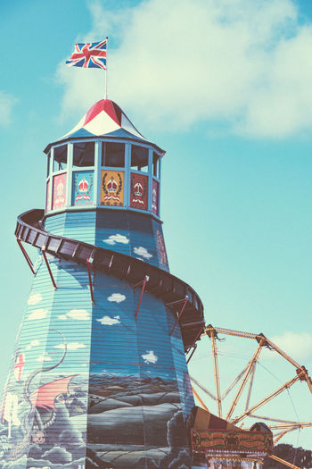 Vintage helter skelter and ferris wheel. Ferris Wheel Funfair Helter Skelter Architecture Arts Culture And Entertainment Big Wheel Building Building Exterior Built Structure Cloud - Sky Day Fairground Flag History Low Angle View Nature No People Outdoors Patriotism Sky Sunlight The Past Tower Travel Destinations Vintage Fair