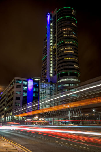 Light trails on road against buildings at night