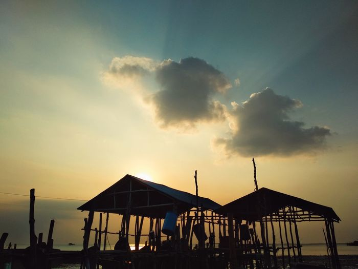 Golden Hour Cloud Sundown Sunlight Backgrounds Cloud - Sky Outdoors Seascape Wooden Nature Natural Phenomenon Silhouette Silhouettes Beach Sunset Summer Fun Sea Silhouette Water Sky Shore Thatched Roof Sunshade Horizon Over Water Calm Ocean Hut Stilt House