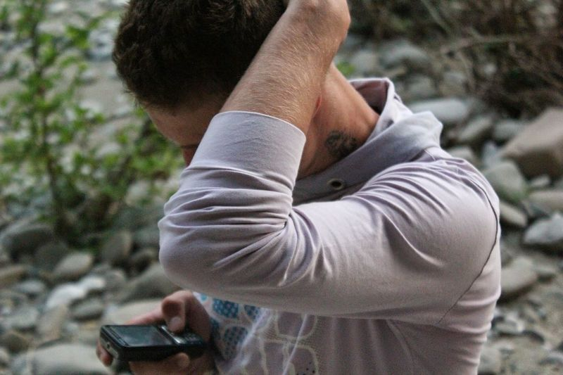 Man Using Mobile Phone With Hand In Hair