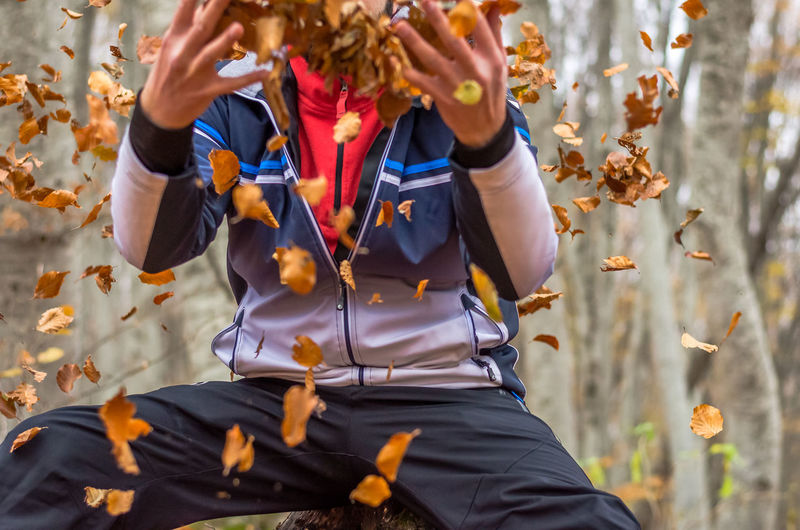 Midsection of man throwing dry leaves in forest