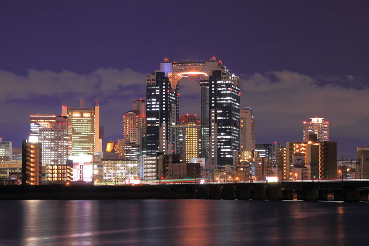 Illuminated umeda sky building in front of river against sky at dusk in city