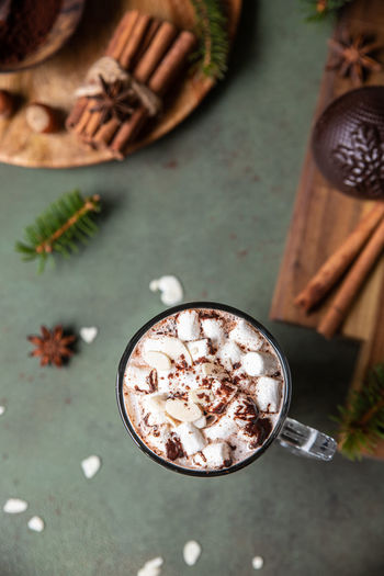 Hot chocolate with marshmallow and cocoa bomb. winter composition with fir branches and spices.