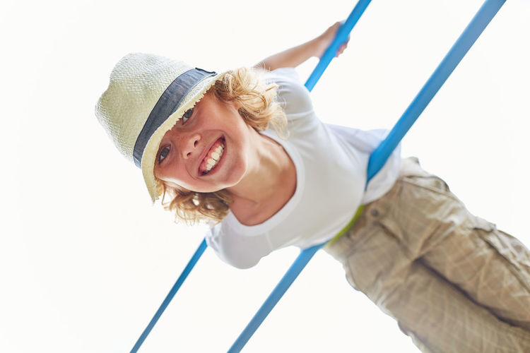 Portrait Of Smiling Boy Hanging From Rod Against Clear Sky