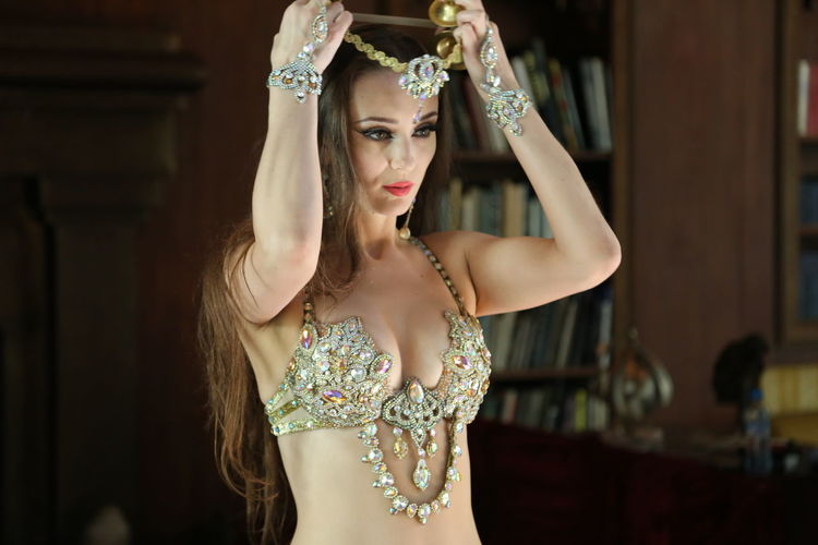 Portrait of beautiful  bellydancer wearing her belly dancing outfit and standing