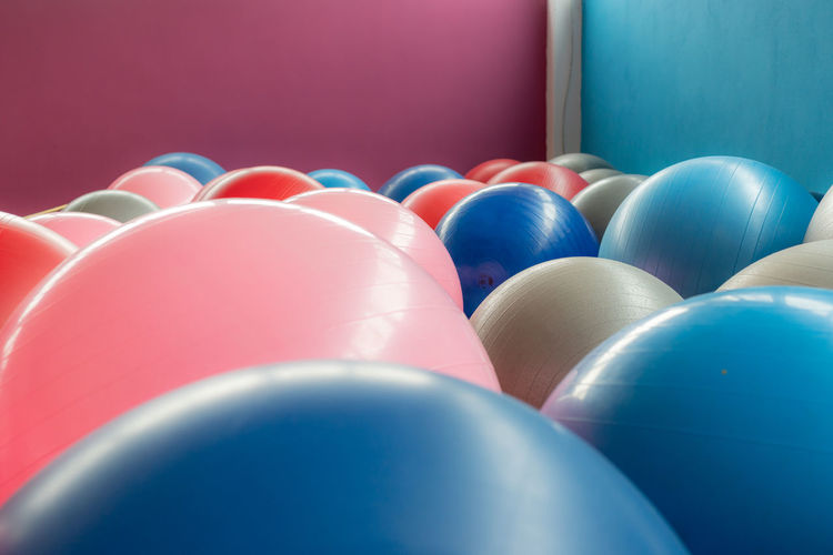 Many different colored exercise balls Exercise Balls Multi Colored Blue Celebration Large Group Of Objects Indoors  No People Close-up Studio Shot Sphere Balloon Pink Color Red Shiny Purple Event In A Row Ball Arts Culture And Entertainment Repetition Blue Background