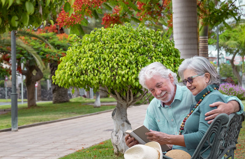 Smiling senior couple sitting on bench reading book at park