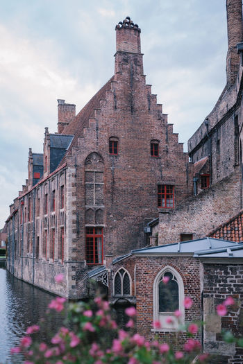 View of old building by canal against sky
