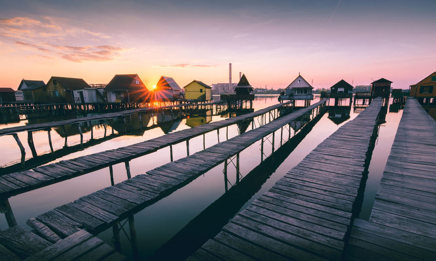 famous floating houses in bokod hungary at sunset Sky Sunset Water Architecture Built Structure Orange Color Building Exterior Nature Scenics - Nature Sea Cloud - Sky Beauty In Nature Sun No People Pier City Railing Outdoors Reflection Floating On Water