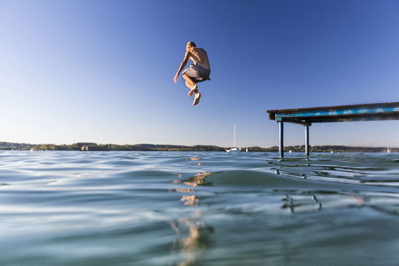 Man jumping in water against clear sky