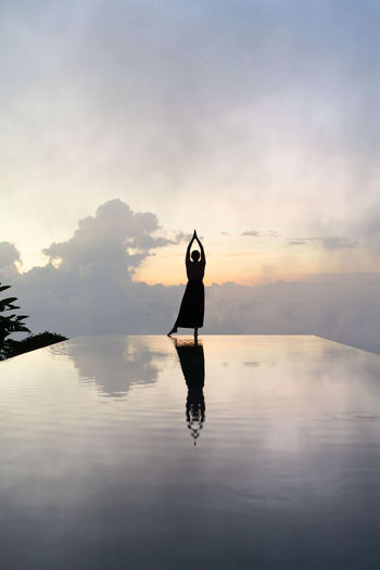 One Person Sky Water Reflection Leisure Activity Beauty In Nature Real People Scenics - Nature Tranquility Lifestyles Tranquil Scene Sunset Standing Nature Cloud - Sky Silhouette Waterfront Adult Full Length Human Arm Arms Raised Capture Tomorrow