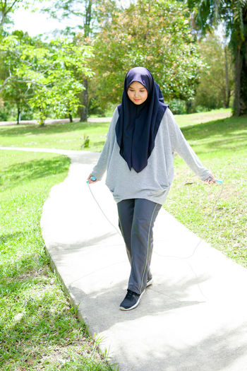 Full length portrait of young woman standing in park