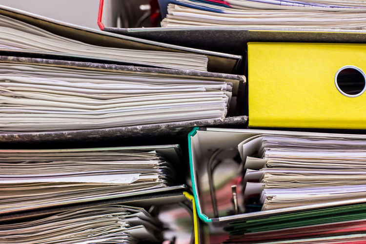 Full frame shot of stacked papers in files at office