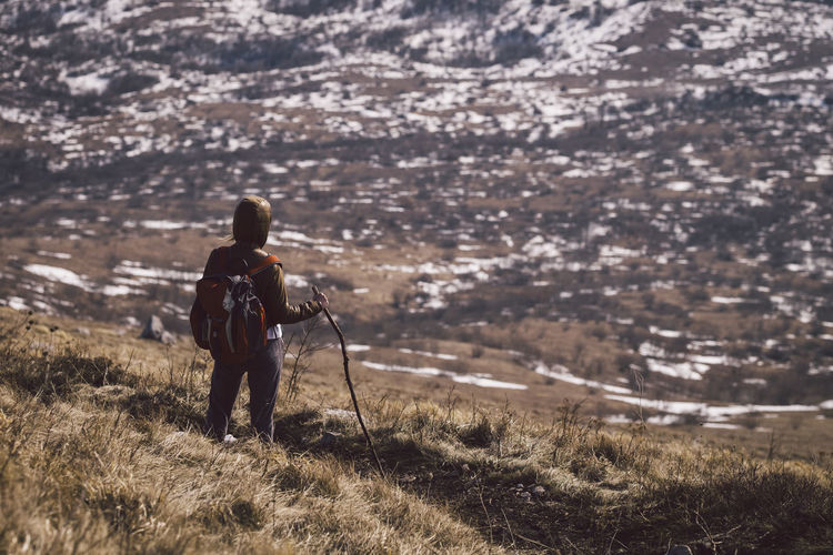 Rear view of backpack hiker standing on mountain against landscape during winter