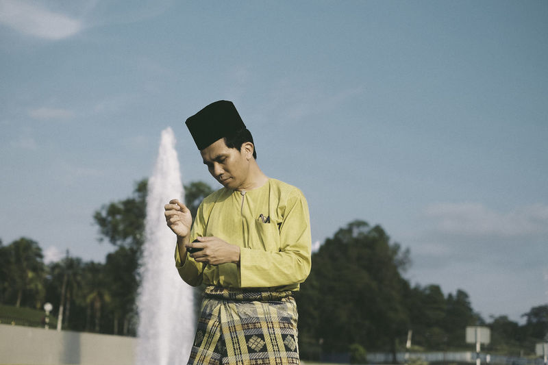 A man in Malay costume Casual Clothing Cloud - Sky Communication Day Front View Holding Leisure Activity Lifestyles Nature One Person Outdoors People Real People Sky Standing That's Me Tree Wireless Technology Young Adult