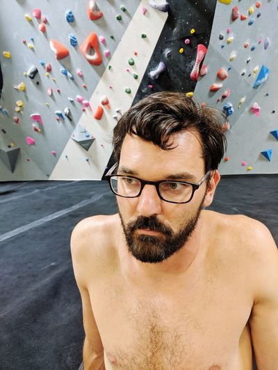 Shirtless man sitting against climbing wall