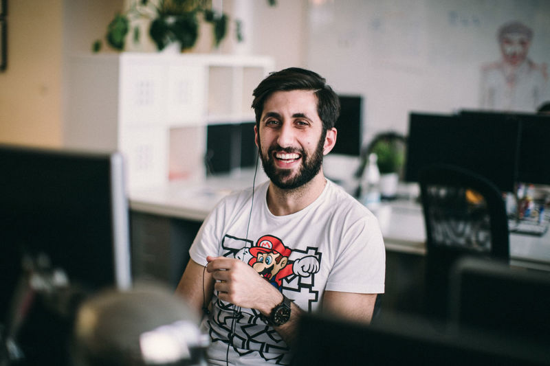 Facial Hair Young Adult Real People Beard Young Men One Person Indoors  Smiling Furniture Portrait Office Computer Men Creativity Desk Waist Up Casual Clothing Table Front View Mustache New Business