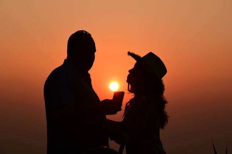 Silhouette man and woman standing against orange sky during sunset