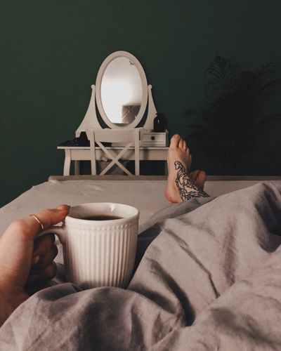 Man holding coffee cup on bed