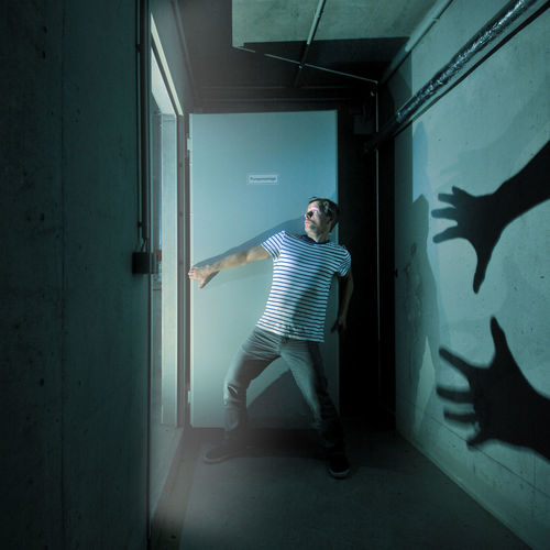 Scared Man With Shadow On Wall Standing In Darkroom
