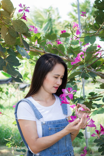 Beautiful young woman standing by flowering plants