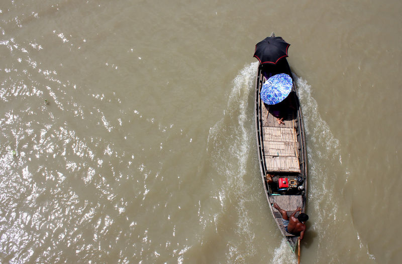 High Angle View Of People On Boat In River During Sunny Day
