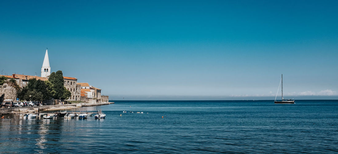 Sailboats in sea by buildings against clear blue sky