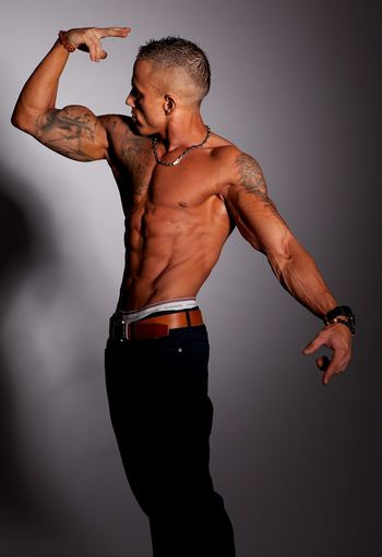 Shirtless Young Man Flexing Muscles While Standing Against Wall