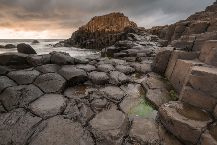 Giants causeway against cloudy sky