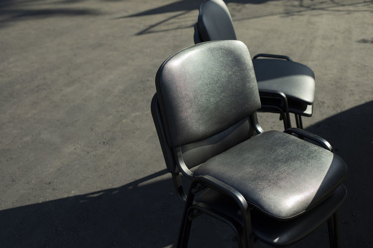 High angle view of empty chair on street during sunny day