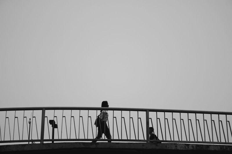 Silhouette people walking on footbridge against clear sky
