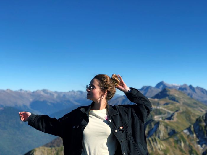 Woman with arms raised standing against mountain and clear blue sky