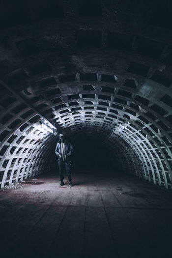 Man wearing hoodie standing in tunnel