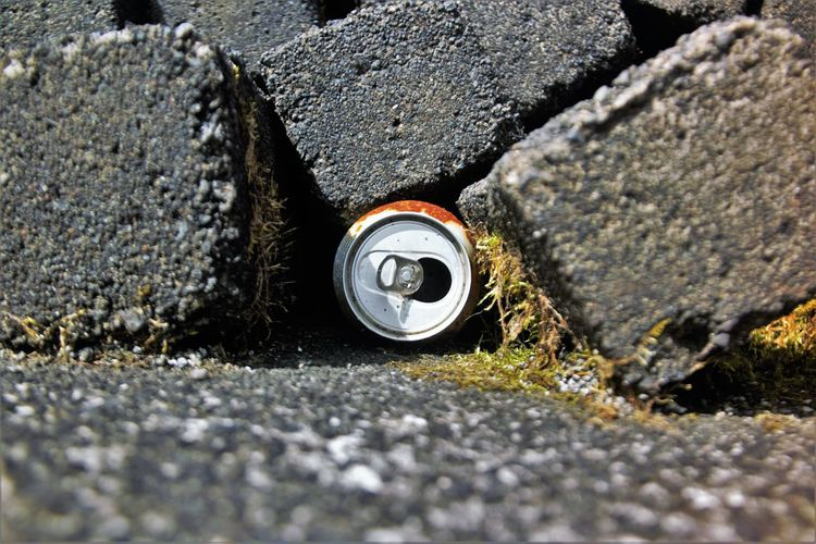 Close-up of can amidst rock