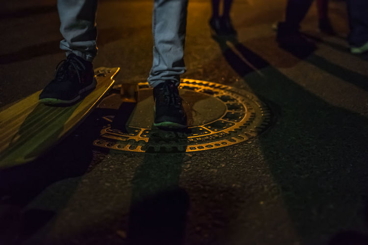 Low section of man on skateboard at night